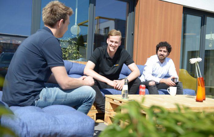 Drei Mitarbeitende sitzen auf der Palettenlounge