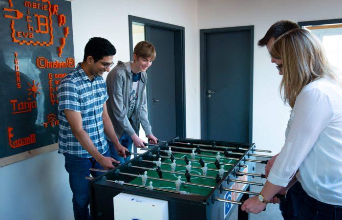 4 Mitarbeiter spielen Kickerfußball